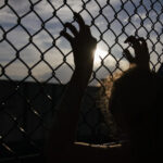 [Image description: silhouette of a girl gripping a fence with two hands.] via Unsplash