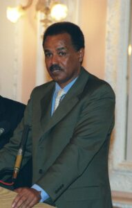 [Image description: President of Eritrea, Isaias Afwerki, standing in front of a podium, 2002.] via Wikimedia Commons