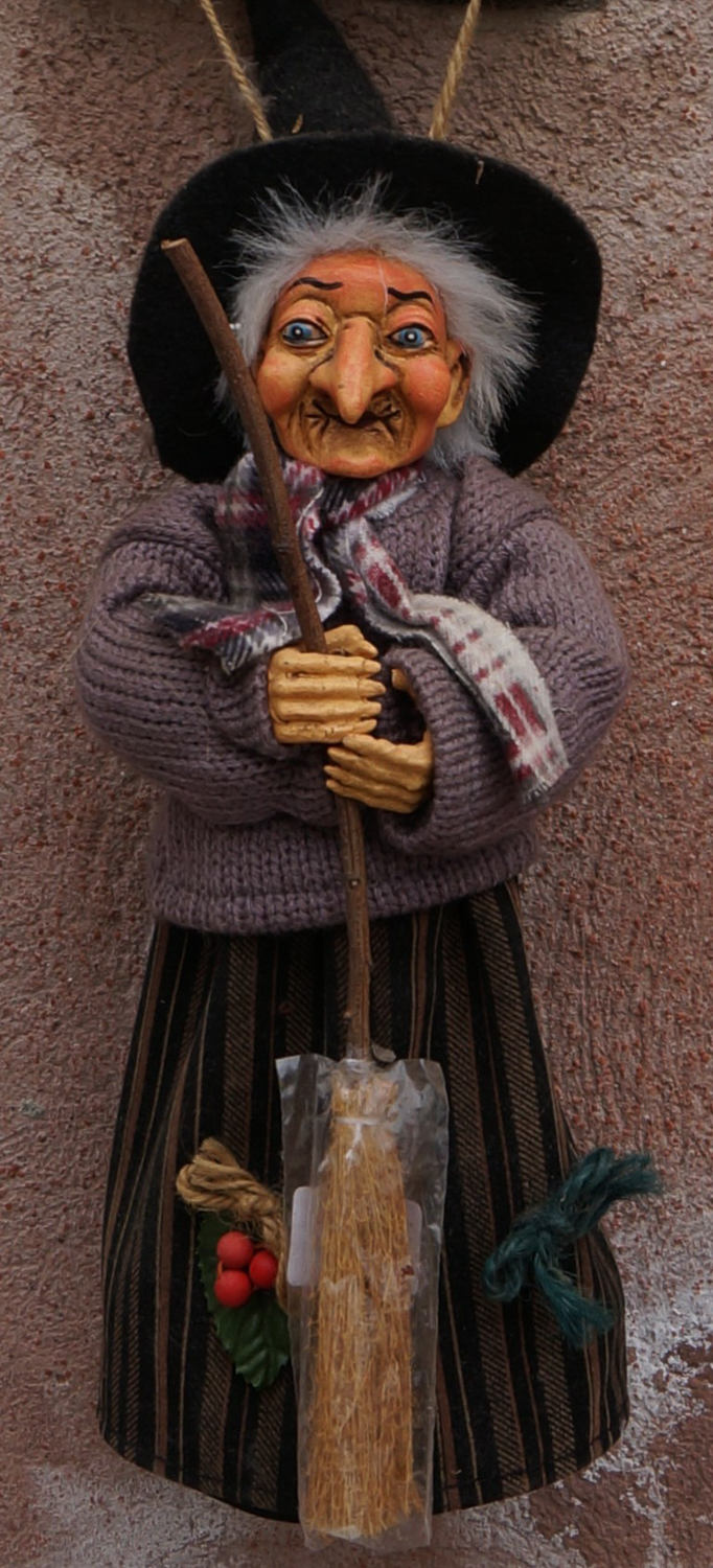 A small figurine of La Befana, portrayed as an elderly witch wearing a green witch's hat and holding a broomstick.