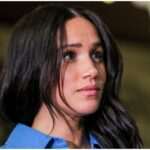 [Image Description: A photograph of Meghan Markle. Her hair is open and her strands of black hair fall on her face.] via AP