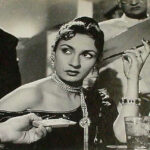 Black and white photo of actress Nadira in the film Shree 420. Nadira is wearing a black dress and long necklace with her hair up, holding a cigarette holder, surrounded by people.