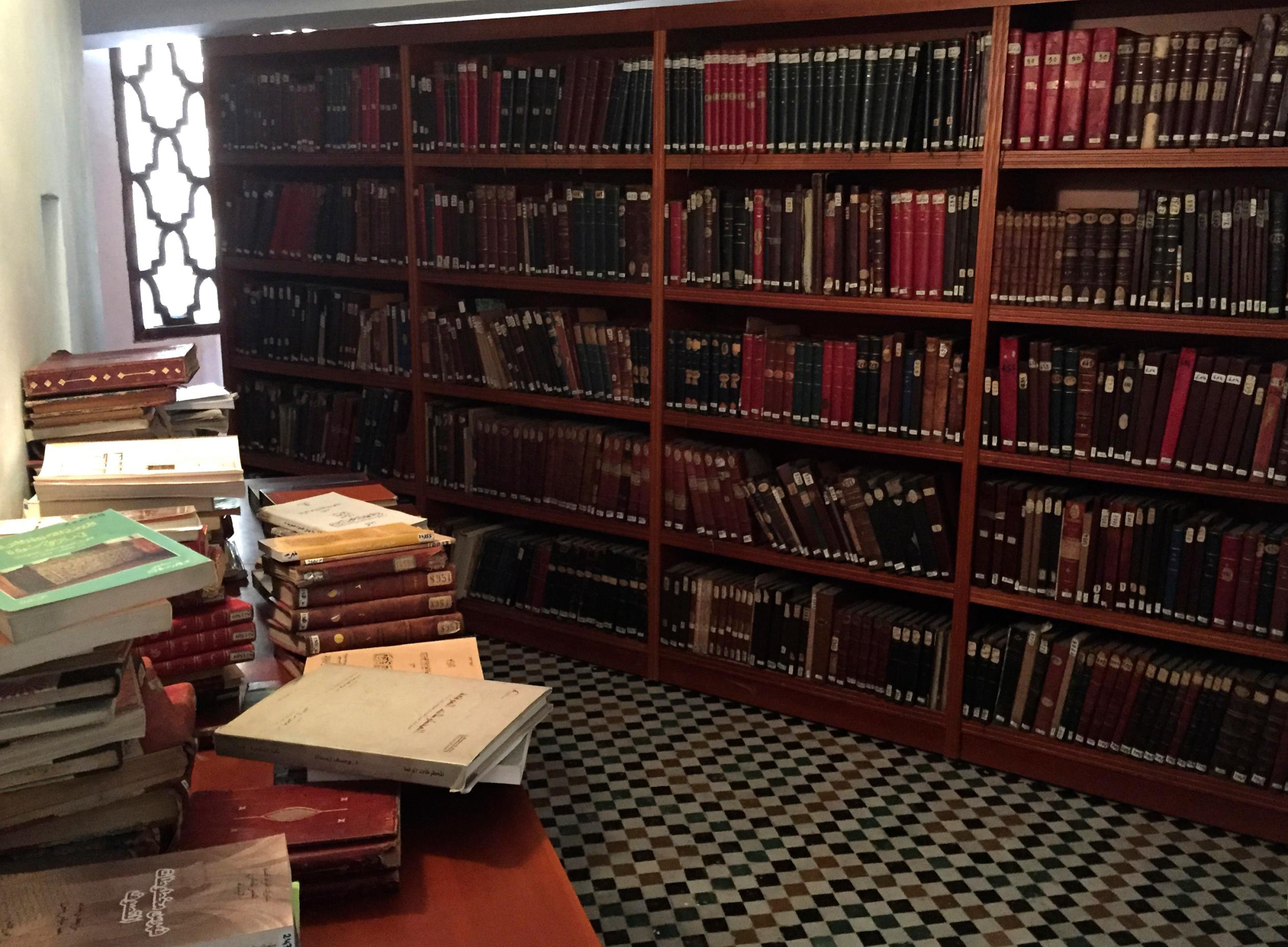 Corner of a library at University of Al Qarawiyyin, with books on shelves and stacks of books on tables