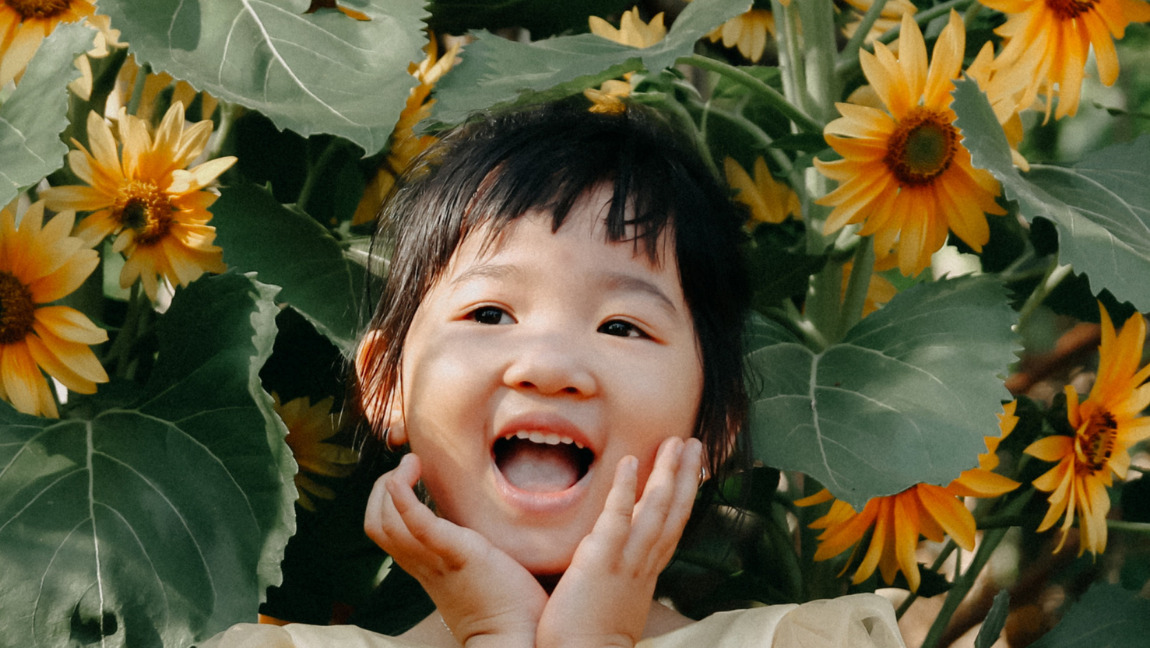 A girl smiling in a field of sunflowers
