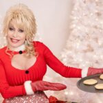 [Image description: Dolly Parton dressed in a red Christmas outfit and holding a tray of cookies.] Via Butterfly Records