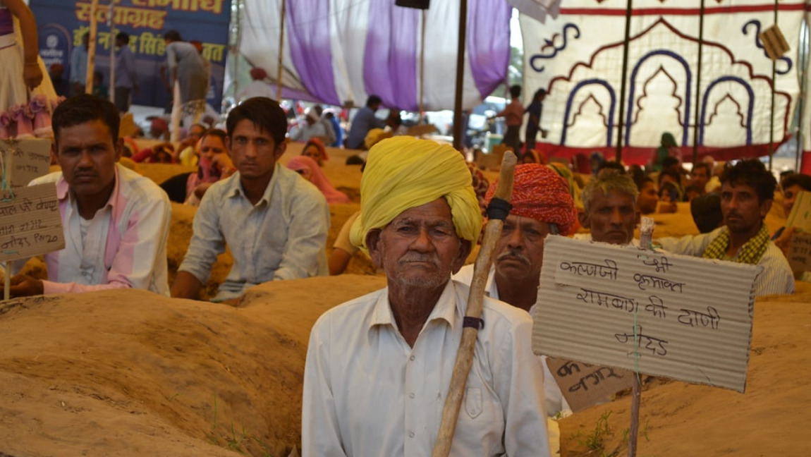 [Image Description: Farmers in Rajasthan protest government land acquisition] Via Unsplash