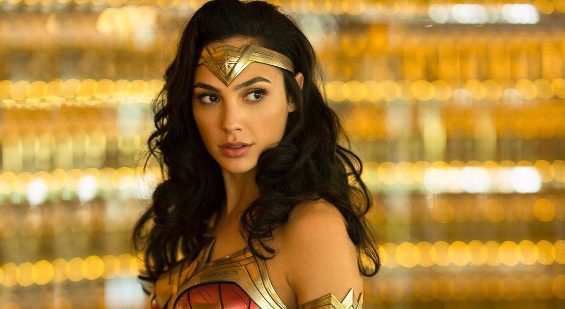 Gal Gadot is dressed as Wonder Woman with a gold head piece and red armor. Her hair is long and dark. The background behind her is gold and she looking over her shoulder to the right.