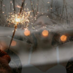 [Image description: A girl holds her face in the background and a sparkler glitters in the foreground.]