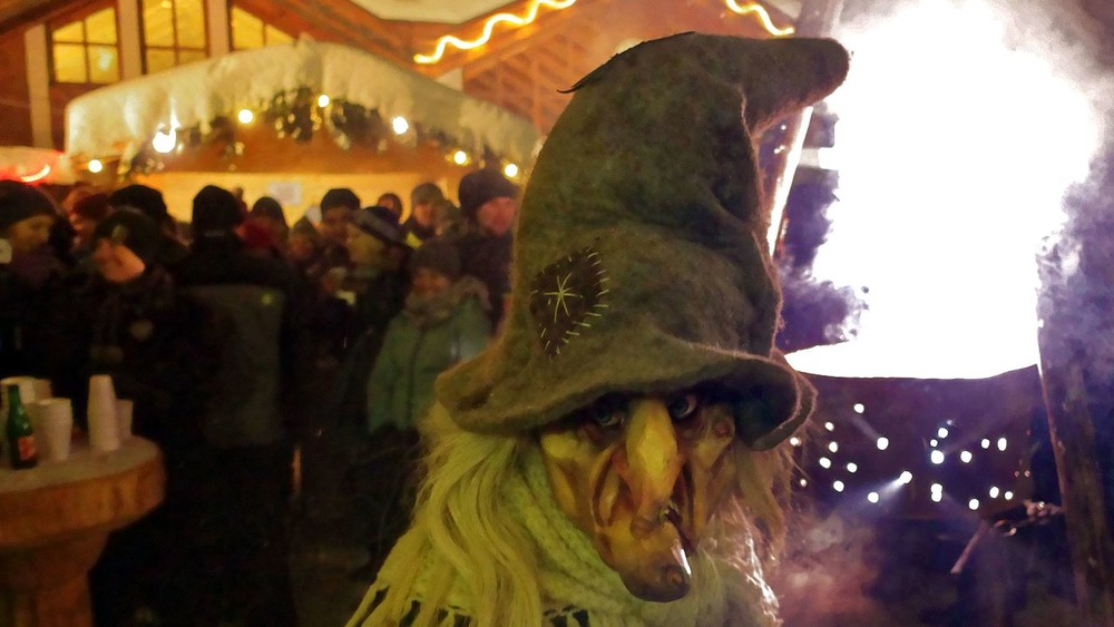 A person wearing a witch's mask with exaggerated features like a long nose and fierce eyes looks at the camera. They are wearing a long witch's hat.