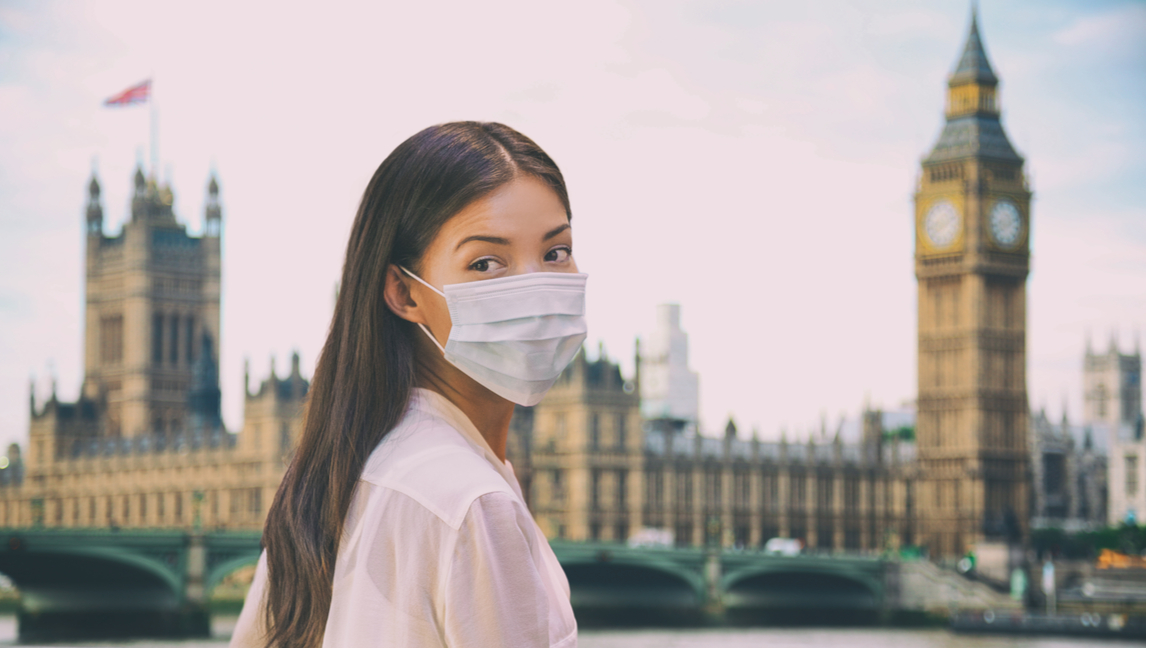 [Image description: A woman wearing a mask next to the Big Ben in London.] Via Shutterstock