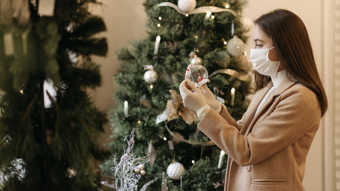 A woman wearing a mask stands in front of a Christmas tree, holding a Christmas decoration.