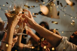 A group of people holding up wine glasses and doing a toast. They are surrounded by gold confetti.