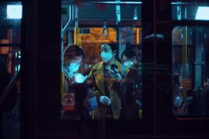 Three Asian women on a train wearing masks at night.