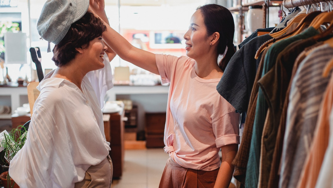 A woman playfully tries on a beret on her friend's head, while shopping at a store.