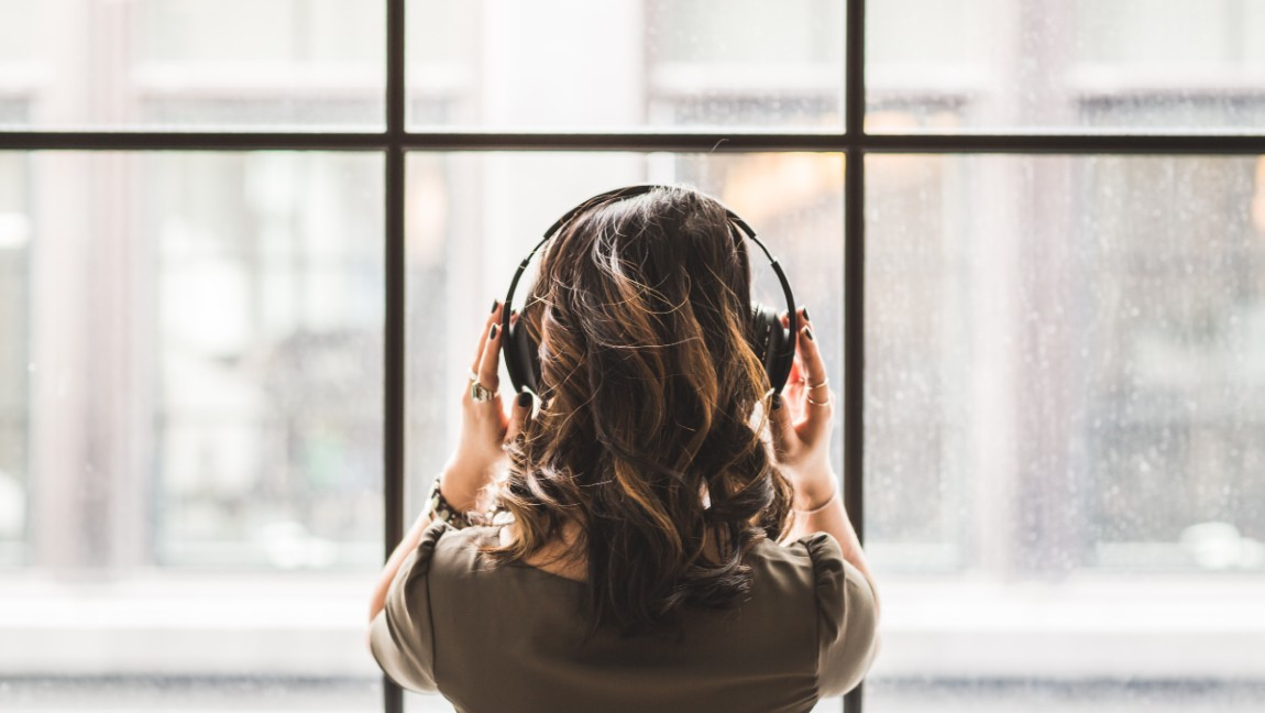 A woman listens to music with headphones in front of a window.