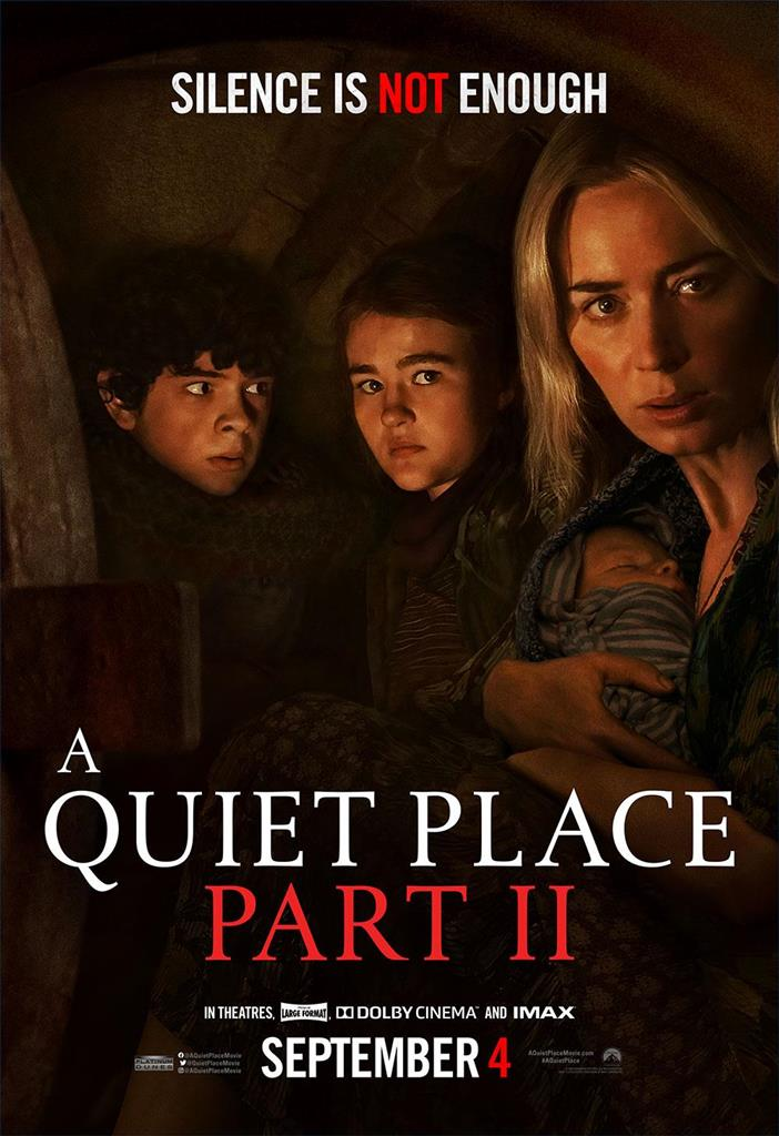 A Quiet Place Part II movie poster where a women is holding a sleeping baby in her arms and two young kids are behind her and they all seem to be in a dark cave