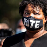 "[Image description: Stacey Abrams wearing a mask that says, ""vote.""] Via essence.com"