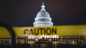 [Image Description: A distant photo of the US Capitol building, with a yellow caution tape around it] Via Unsplash