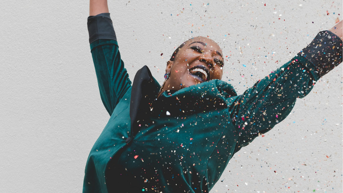A young woman jumping in joy with glitter falling down on her