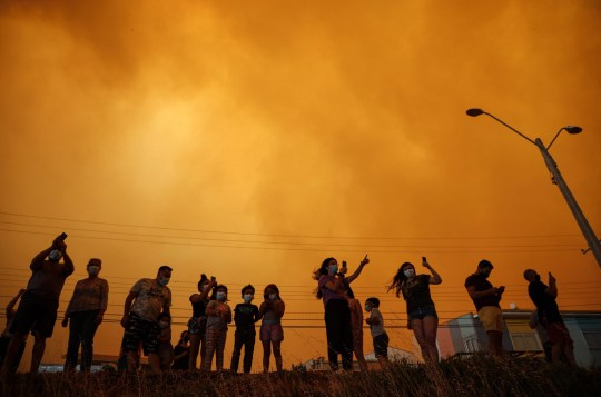 [Image Description: Residents look up at the orange sky as the wildfires burn nearby (Picture: AP)] Via AP
