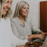 [Image Description: Two white women work on MacBooks at an office while laughing] Via Unsplash