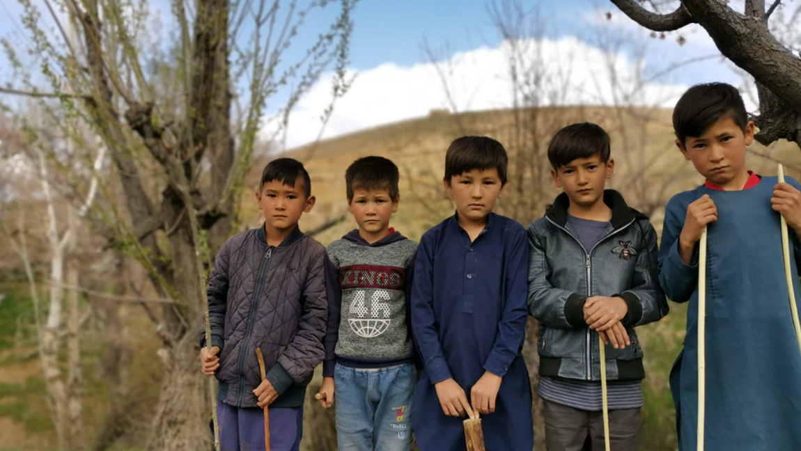 [Image Description: A group of Hazara Muslim boys stand and pose for a photo, their expressions solemn] Via Unsplash