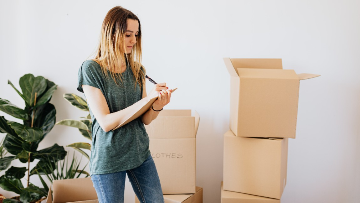 A woman packs boxes for moving.