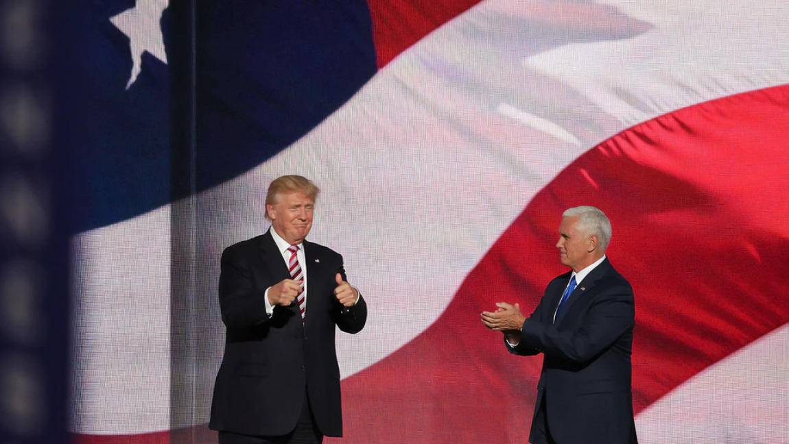 [Image Description: Trump and Pence stand in front of an American flag, clapping] Via Unsplash