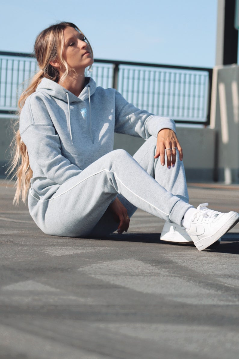 A woman sitting outside wearing gray hoodie and sweatpants and white sneakers.