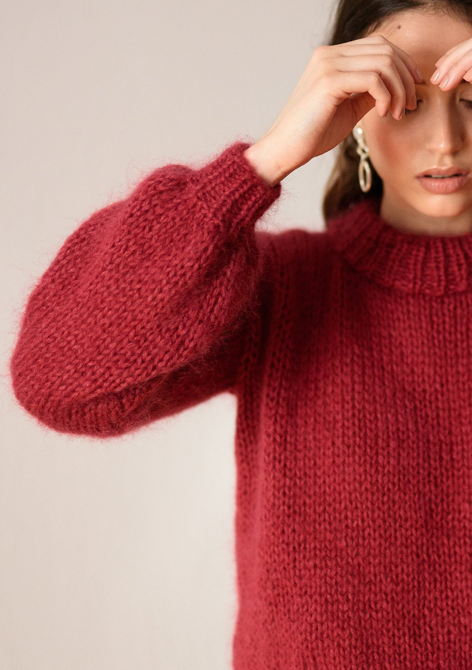 A woman wearing an oversize red knit.