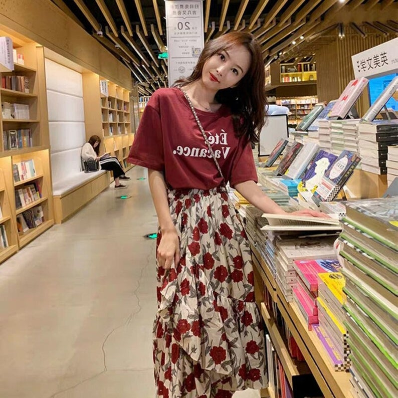 A woman inside a bookshop wearing a red t-shirt and flowy, floral skirt.