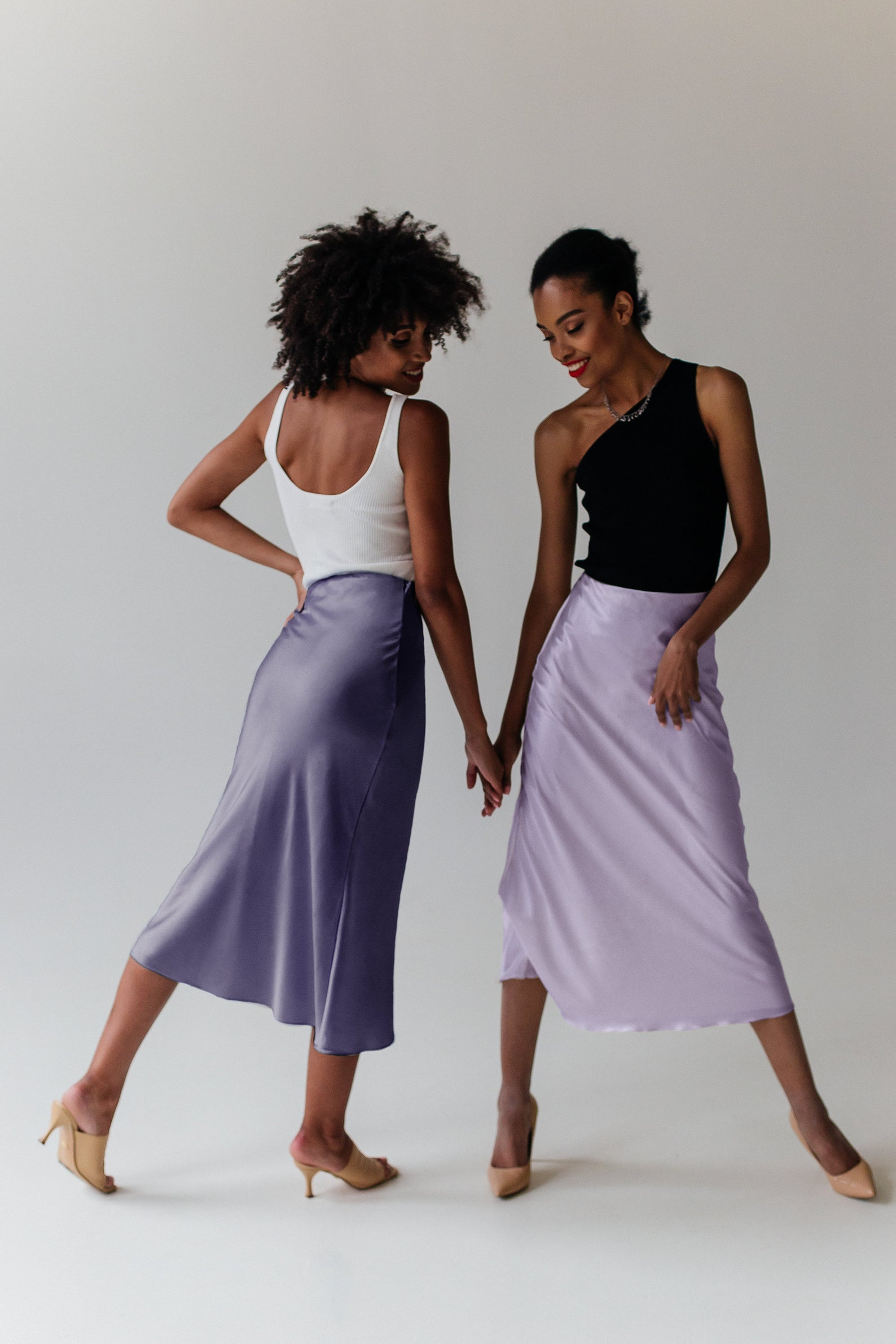 Two women holding hands. Woman on the left wearing dark lilac slip skirt and white top. Woman on the right wearing light lilac skirt and black top.