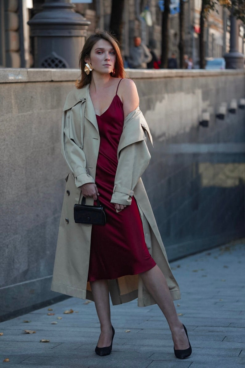 A woman outside wearing a red slip dress and trench coat.