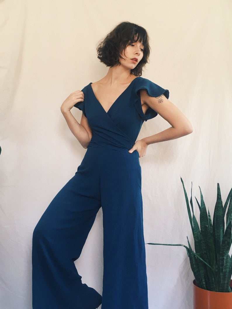A woman wearing a short-sleeved blue jumpsuit.