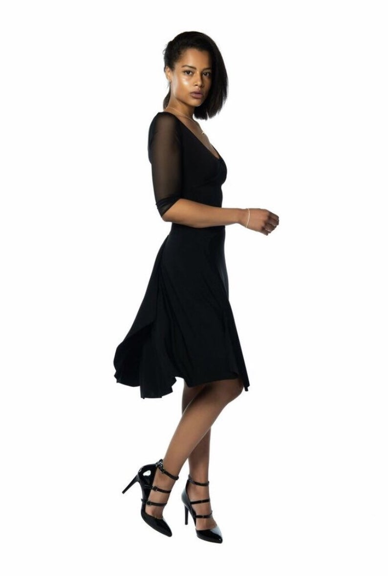 A woman wearing a black dress against a white background.