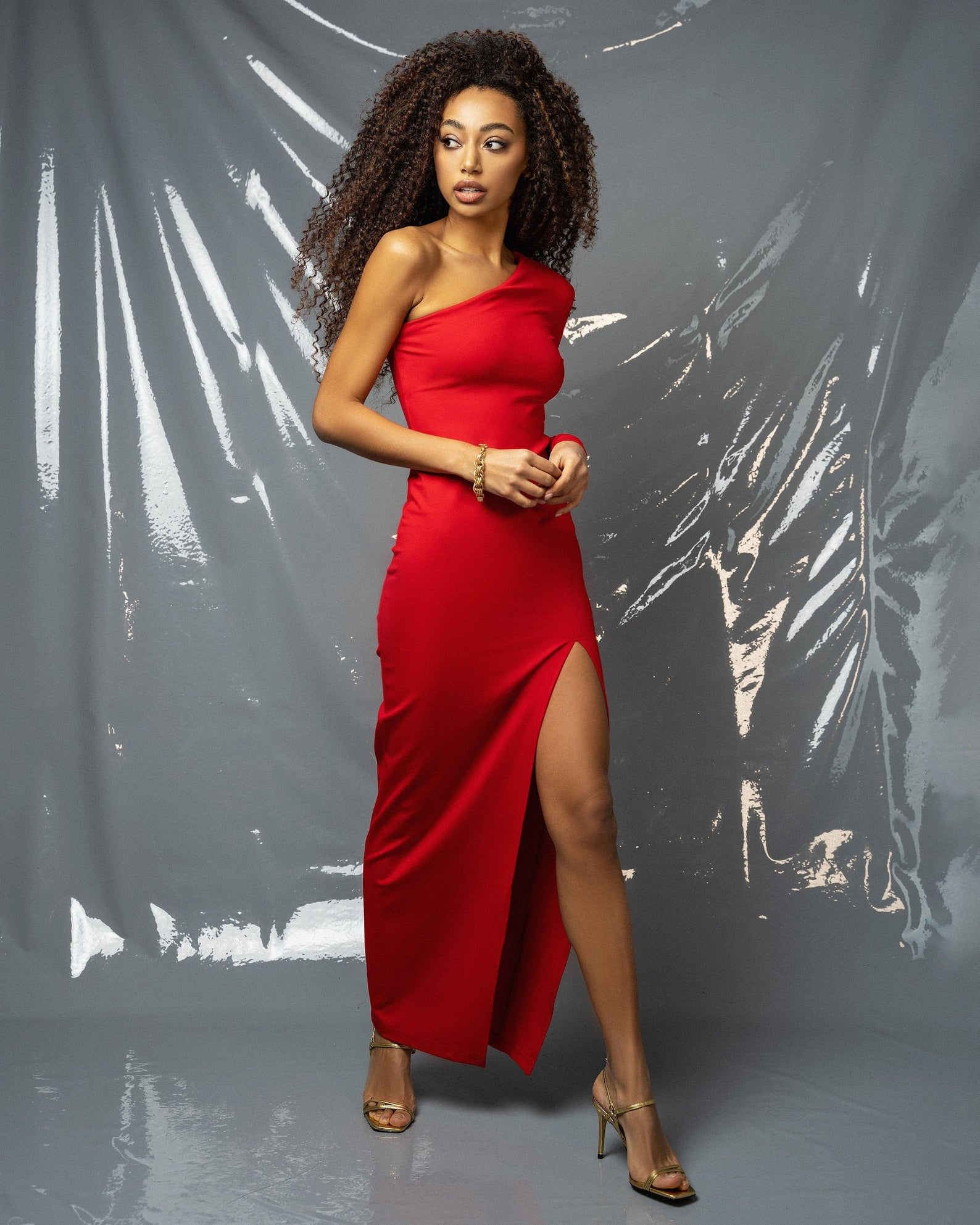 A woman wearing a red one shoulder, thigh-high slit dress.