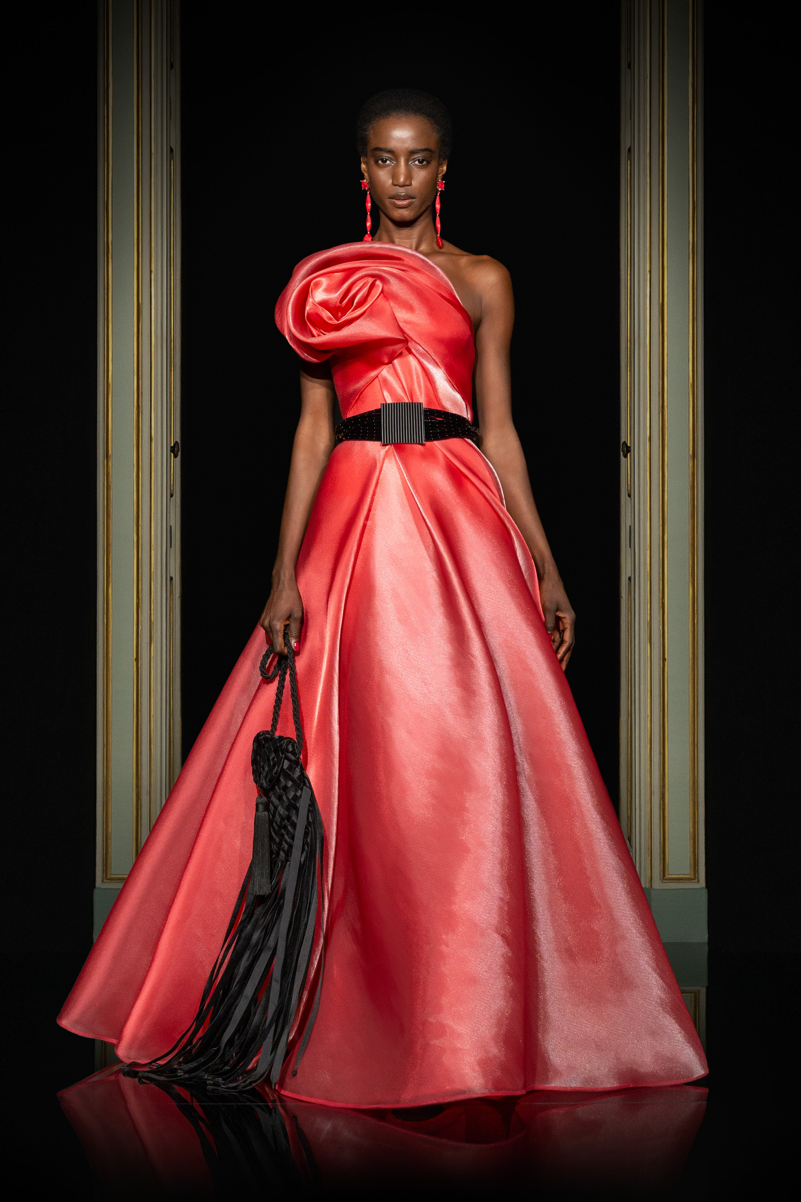 Armani Privé Spring 2021 Couture. A lady wearing a coral red gown and a black belt around the waist.