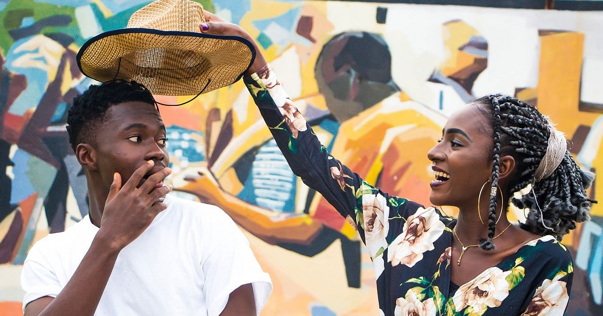 A woman playfully takes off a man's hat and with a look of shock. Via Pexels