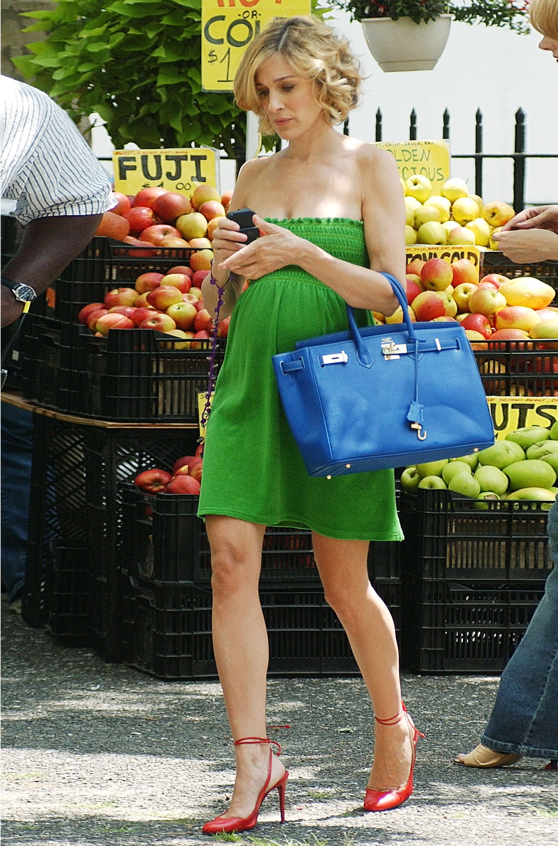 Carrie Bradshaw walking in front of a fruit stall wearing a strapless green dress, holding a blue bag and wearing red slingbacks