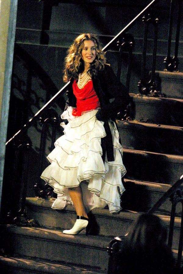 Carrie Bradshaw wearing a white frilled skirt, red top, black jacket and black and white kitten heels