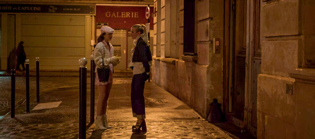 Emily and Camille standing next to each other outside of Emily's apartment. Emily (left) is wearing a plaid white jacket, pink beret and skirt, and white boots. Camille (right) has her hair in a high ponytail and is wearing a white ruffled shirt, wide-leg jeans, and chunky heels.