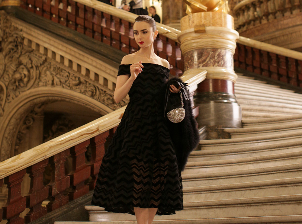 Emily standing on a staircase wearing an off the shoulder black knee-length dress