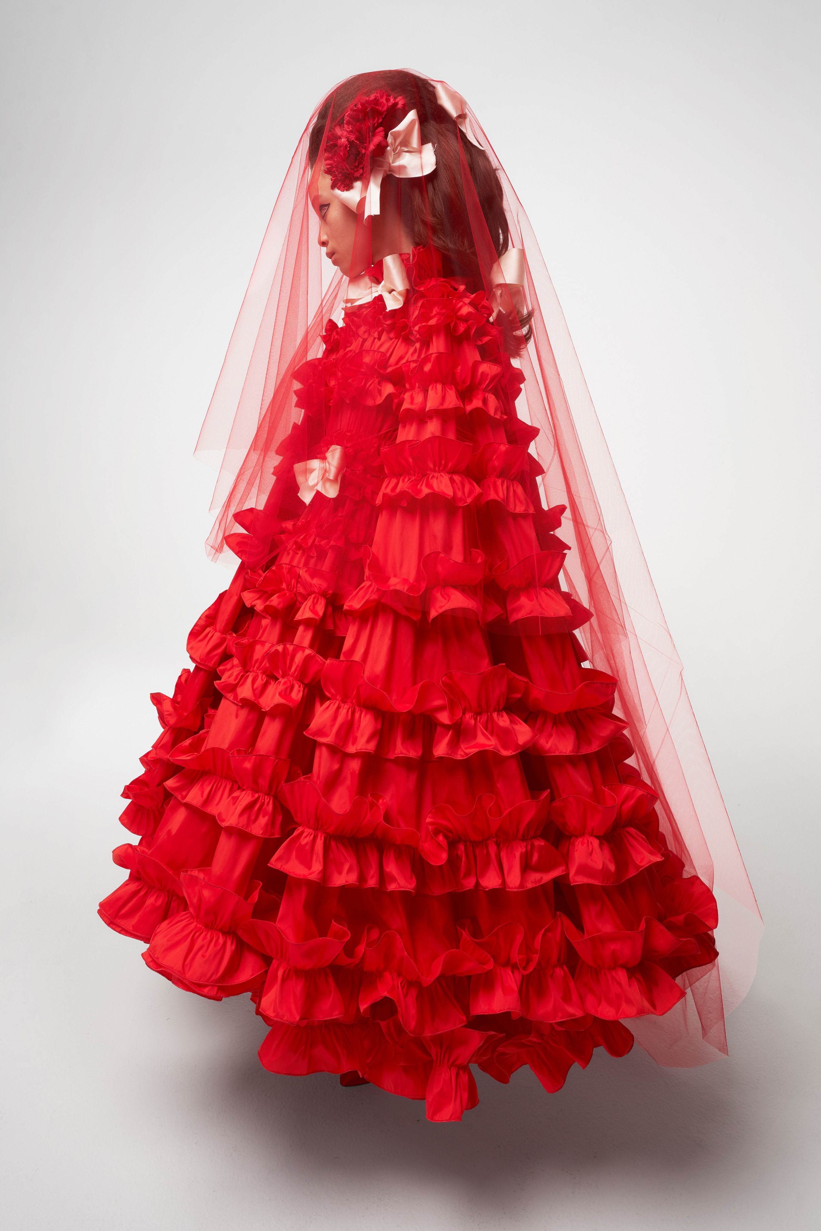Giambattista Valli Spring 2021 Couture. A lady wearing a voluminous ruffled red gown and a sheer red veil over her head.