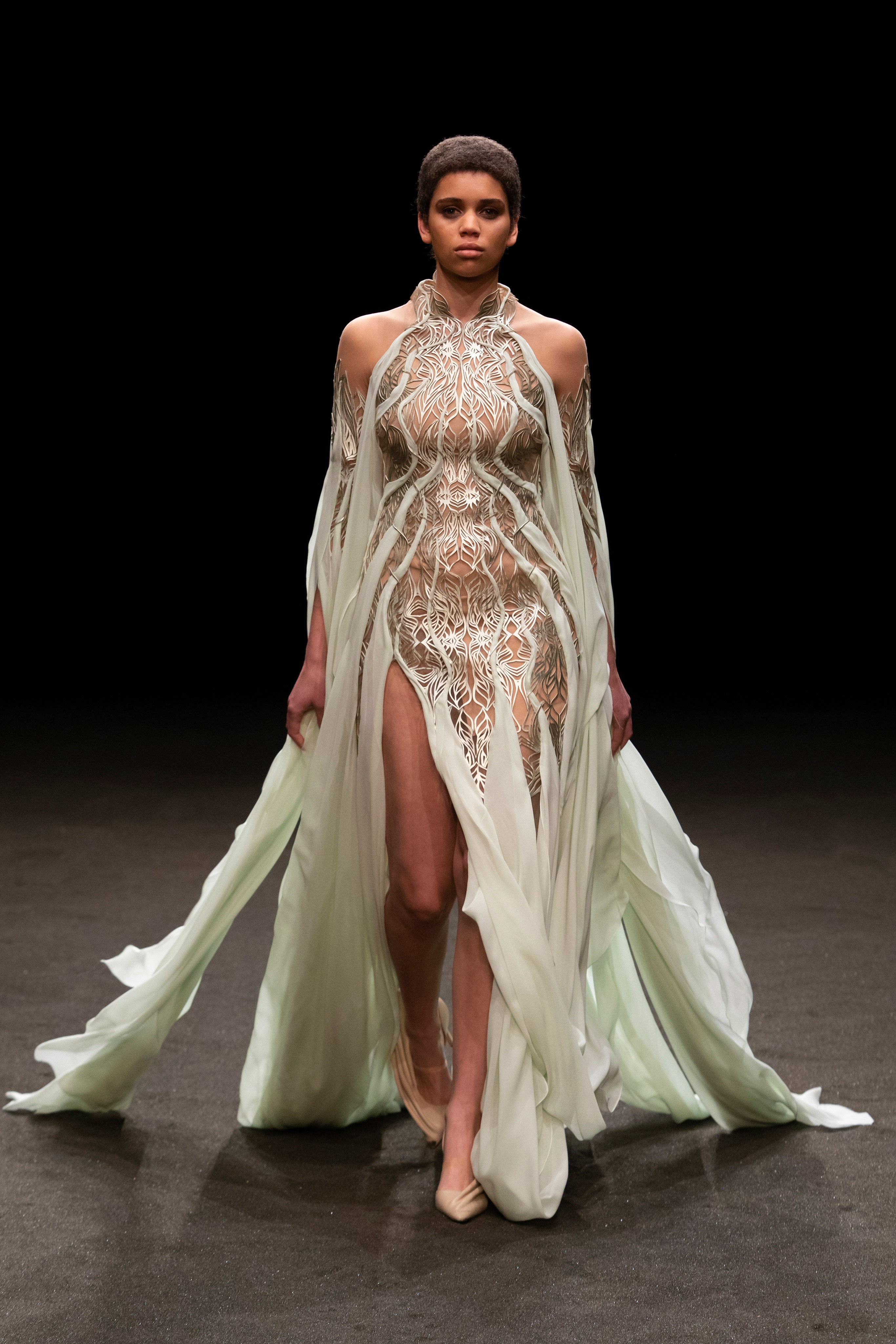 Iris van Herpen Spring 2021 Couture. A lady wearing a mint colored gown with a train and pattern work on the bodice.