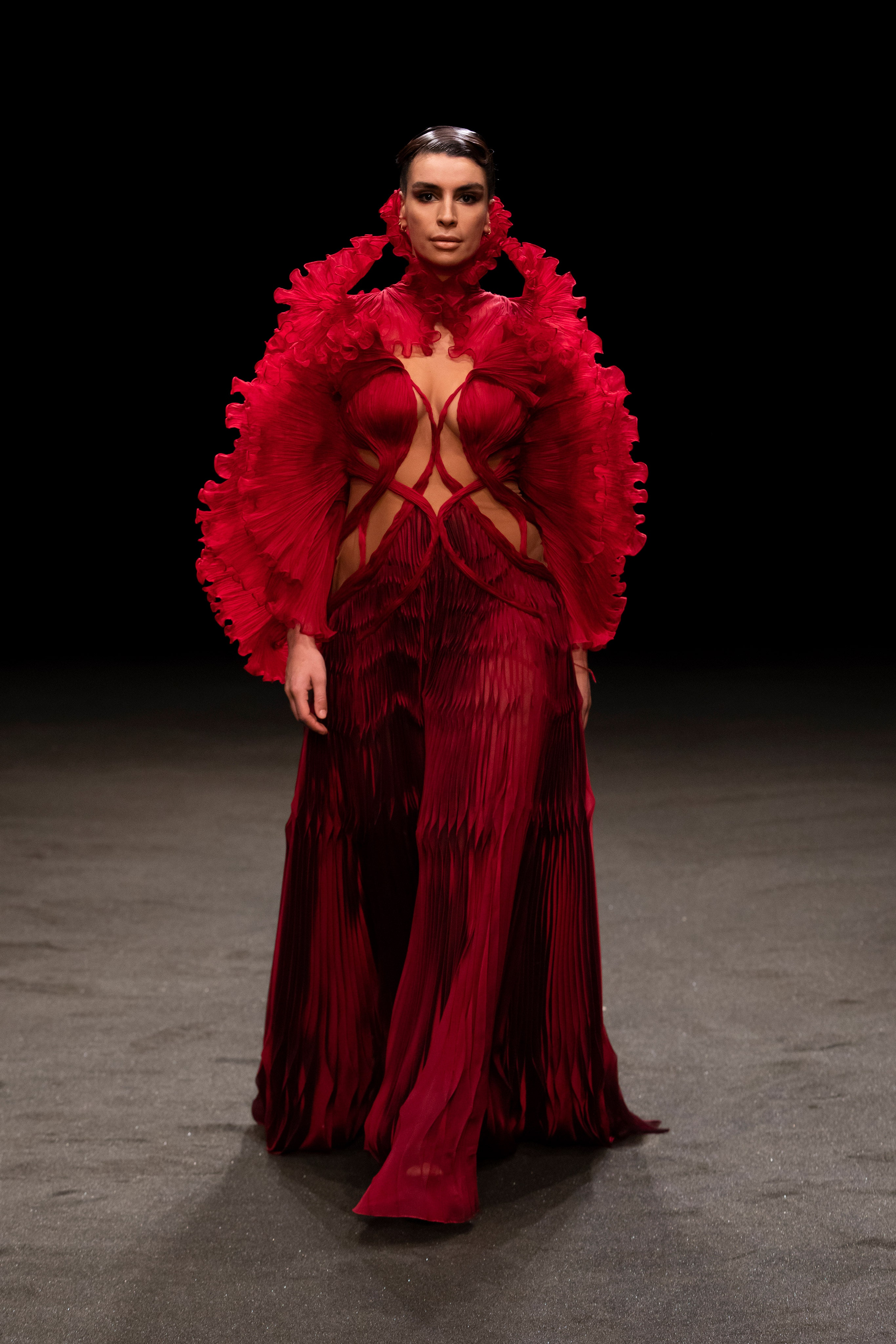 Iris van Herpen Spring 2021 Couture. A lady wearing a deep red gown with ruffles on the neck cascading down to the shoulders and arms.