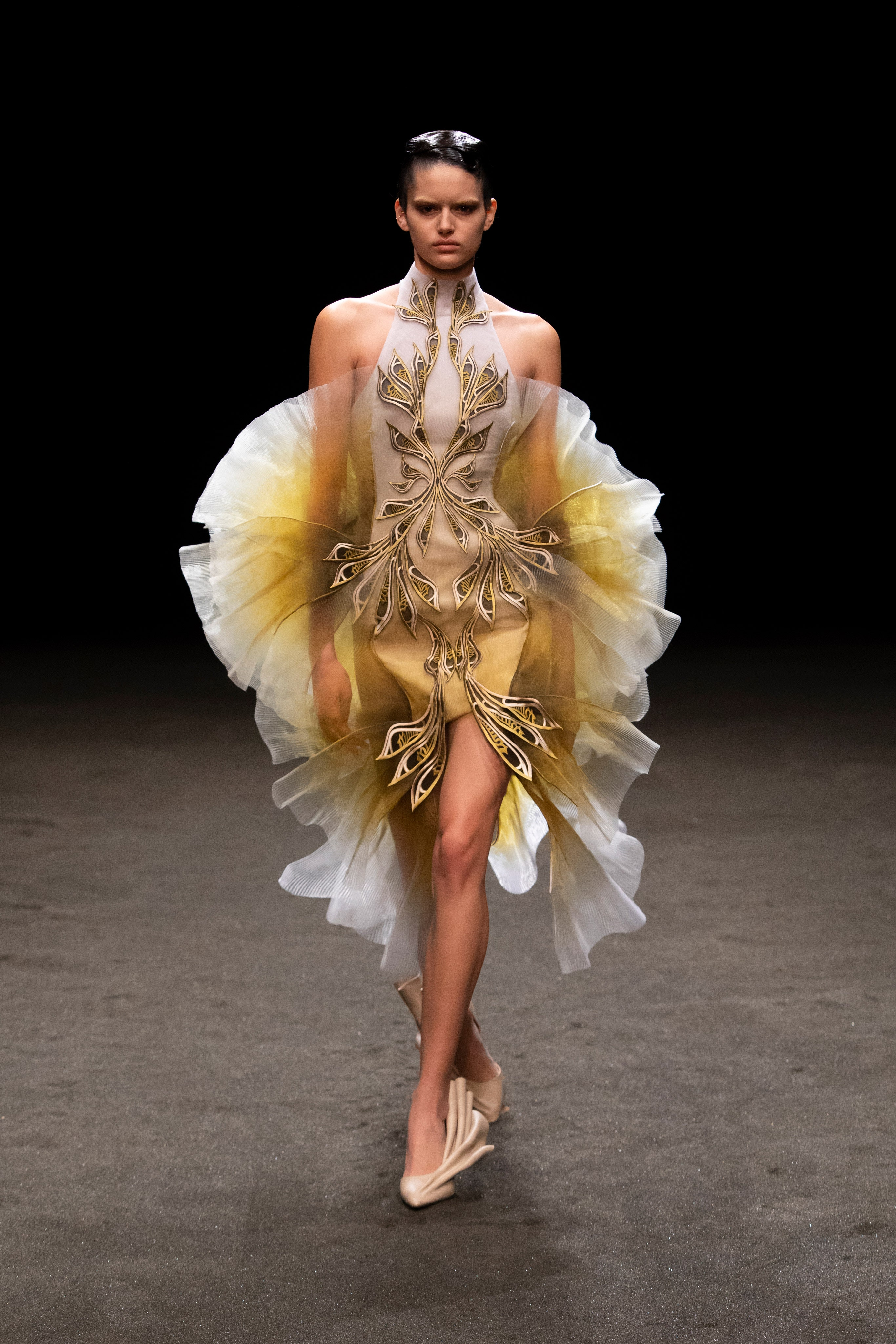 Iris van Herpen Spring 2021 Couture. A lady wearing a beige and yellow dress with a pattern at the center of the dress and ruffles.