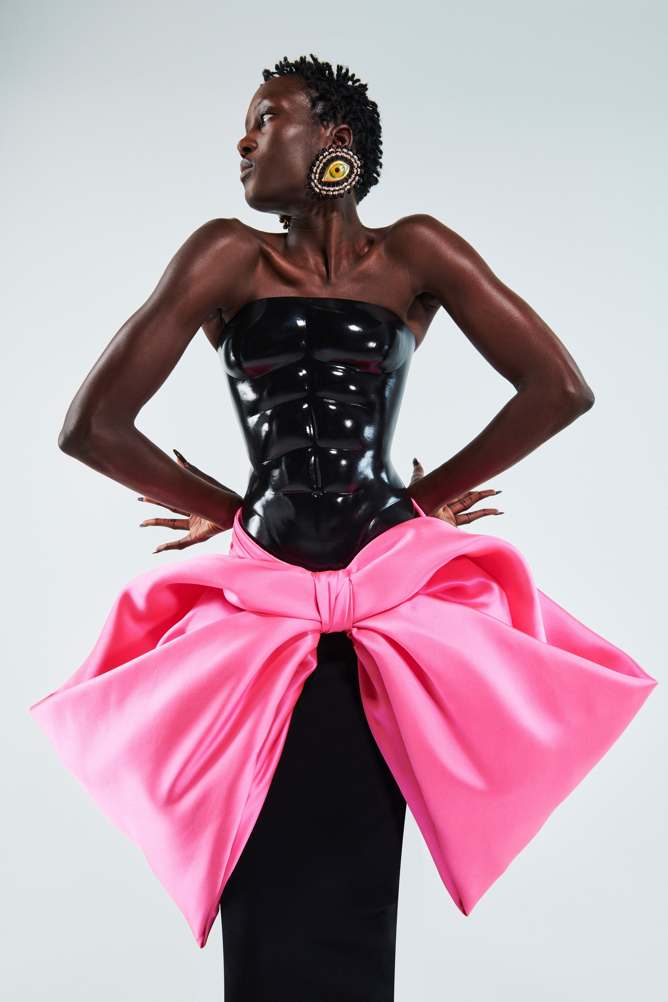 Schiaparelli Spring 2021 Couture. A lady wearing a black six-pack bustier, black skirt and pink bow wrapped around the hips.