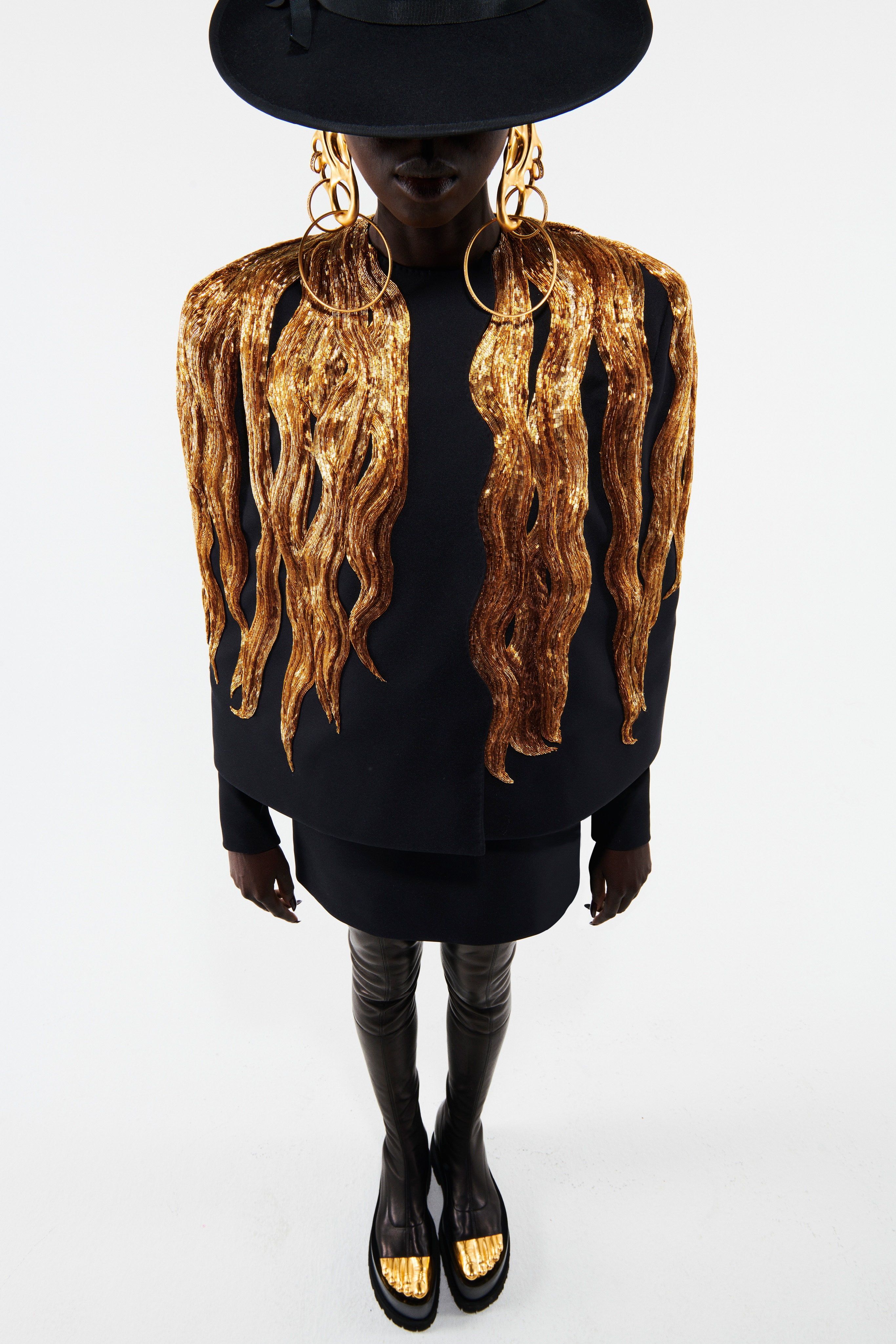 Schiaparelli Spring 2021 Couture. A lady wearing a black dress and jacket with gold embroidery on the jacket.