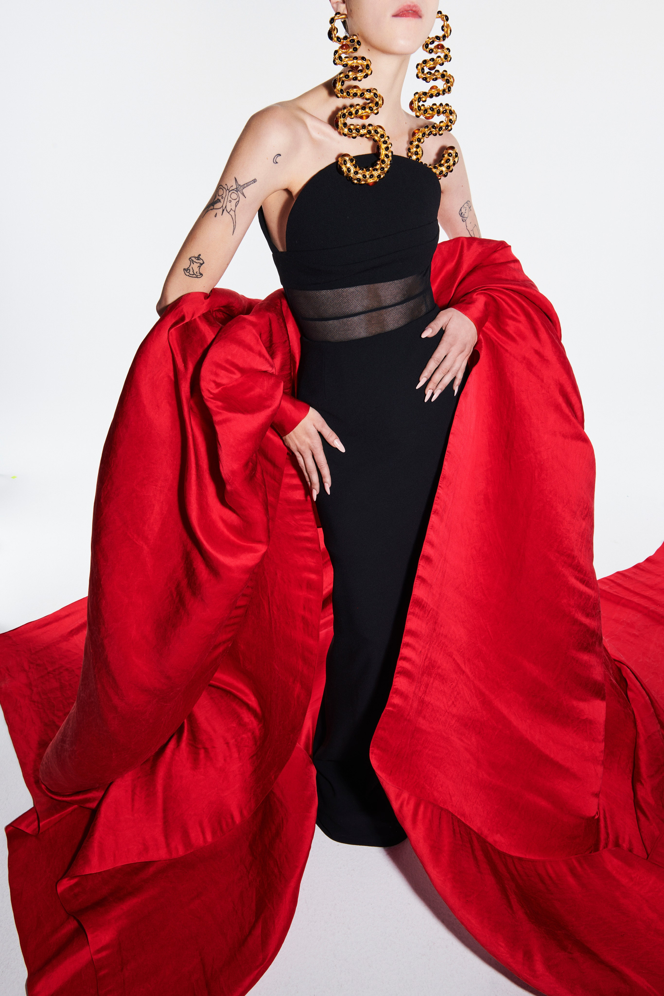 Schiaparelli Spring 2021 Couture. A lady wearing a long black dress with red sleeves that drape down to create a train.