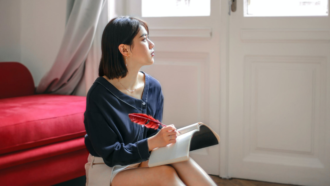 [Image description: Photo of a person sitting in front of a red couch with a notebook in their lap.] Via free photos on Pexels
