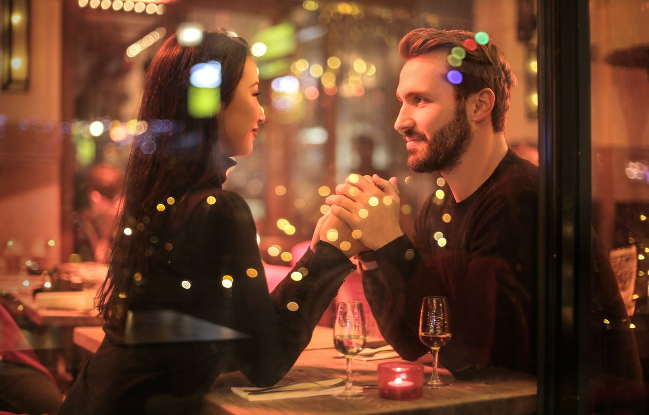 A man and woman holding hands across the table while on a date.